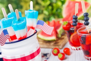 Homemade red-white-and-blue popsicles on an outdoor table.